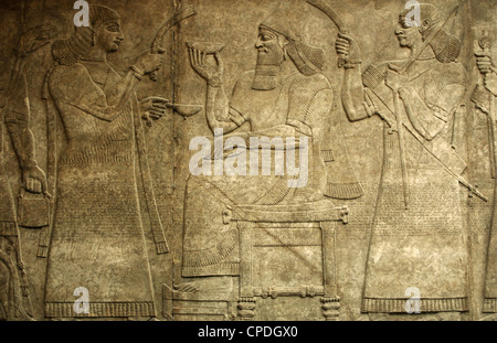 King Ashurnasirpal II seated on his throne between two assistants. 865-860 BC. From Nimrud. Northwest Palace. - Stock Photo