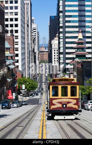 Cable car crossing California Street with Bay Bridge backdrop in San Francisco, California, USA - Stock Photo