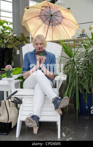 Young blond woman sitting in a chair while shopping, smelling a plant - Stock Photo