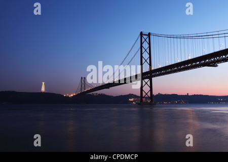 The 25 April Suspension Bridge at dusk over the River Tagus (Rio Tejo), Christus Rei is illuminated at Almada, Lisbon, - Stock Photo