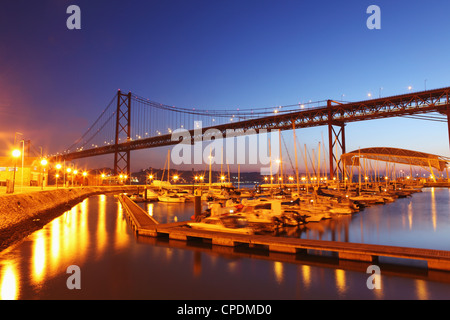 Boats on the River Tagus move at night in the Doca de Santa Amaro marina under the 25 April Bridge, Lisbon, Portugal, - Stock Photo