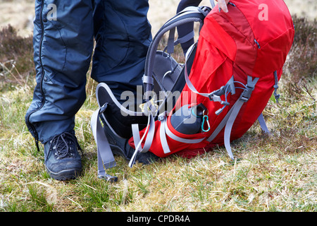 hiker hillwalker wearing boots waterproofs and rucksack in the highlands of Scotland UK - Stock Photo