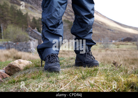 hiker hillwalker wearing boots and waterproof trousers in the highlands of Scotland UK - Stock Photo