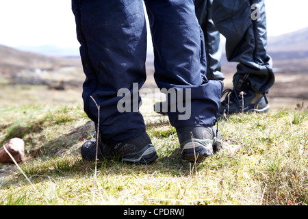 two hikers hillwalkers standing wearing boots and waterproofs in the highlands of Scotland UK - Stock Photo
