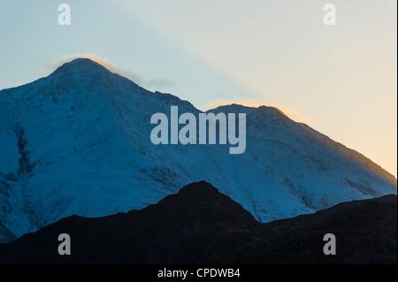 Shaft of golden sunlight on a snowy covered mountain, Glen Sheil, Highlands, Scotland, UK - Stock Photo