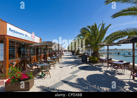 Seafront restaurants by the harbour in the resort of Alvor, near Portimao, Algarve, Portugal - Stock Photo