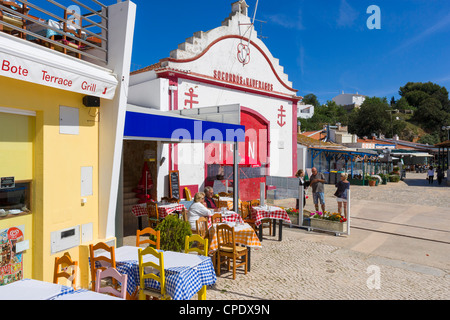 Seafront restaurant by the harbour in the resort of Alvor with lifeboat station behind, near Portimao, Algarve, - Stock Photo