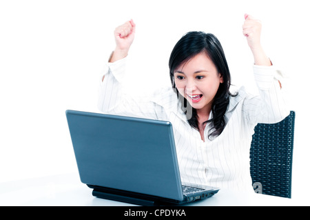 Happy young businesswoman cheering in front of laptop - Stock Photo