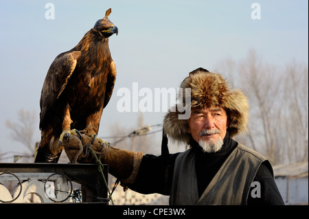 Old kazakh hunter Abylkhak with his golden eagle. - Stock Photo