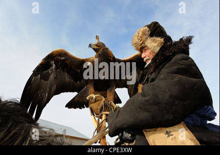 Old kazakh hunter Abylkhak with golden eagle. - Stock Photo