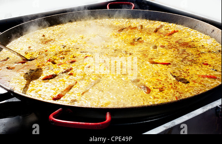 Paella rice typical from Valencia Spain cooking in big pan - Stock Photo