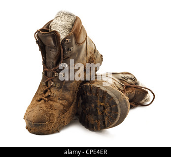 Pair of dirty brown walking boots caked in mud isolated on a white backgound - Stock Photo