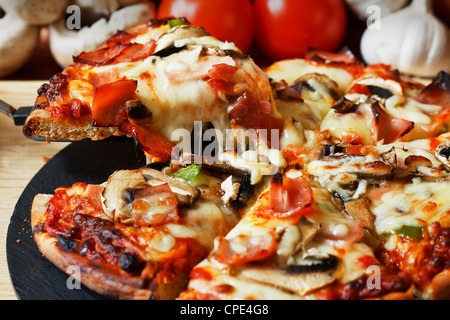serving slice of ham and mushroom pizza with close up on stringy melted mozzarella cheese - Stock Photo