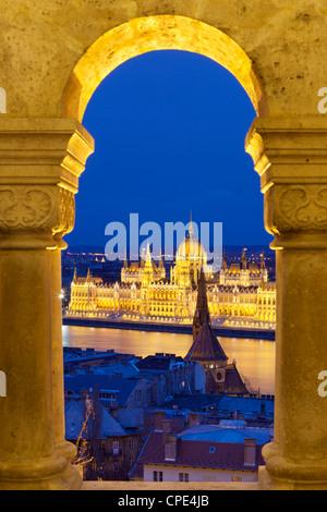 Parliament (Orszaghaz) through arches of Fishermen's Bastion (Halaszbastya) at dusk, Budapest, Hungary, Europe - Stock Photo