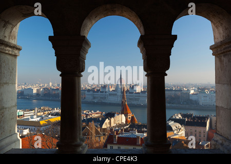 Parliament (Orszaghaz) and River Danube through arches of Fishermen's Bastion (Halaszbastya), Buda, Budapest, Hungary, - Stock Photo
