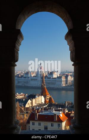 Parliament (Orszaghaz) and River Danube through arches of Fishermen's Bastion (Halaszbastya), Buda, Budapest, Hungary, - Stock Photo