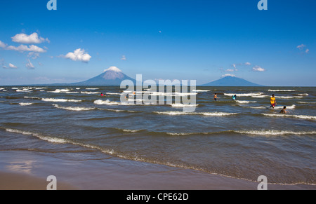 Ometepe Island and swimmers in Lake Nicaragua, Nicaragua, Central America - Stock Photo