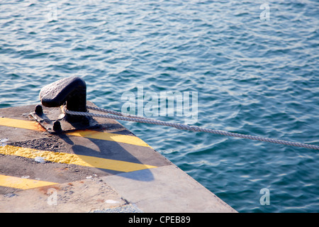 Bollard in port with rope looped around and yellow lines over black - Stock Photo