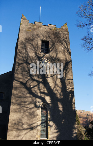 St Oswald's Church Grasmere Cumbria in winter with late afternoon sun casting hard shadows on the church tower - Stock Photo