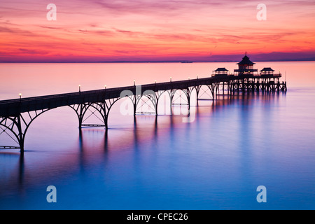The sun sets over the Bristol Channel behind the Pier at Clevedon, Somerset, England, UK