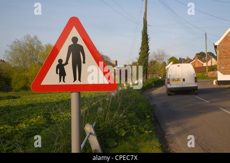 Road sign of adult and child holding hands warns of no pedestrian path through village, Shottisham, Suffolk, England - Stock Photo