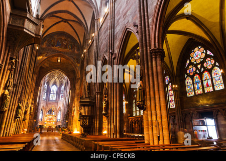 Interior with high ceilings, pillars, stained glass windows, carved decoration figures of gothic Muenster, Freiburg - Stock Photo
