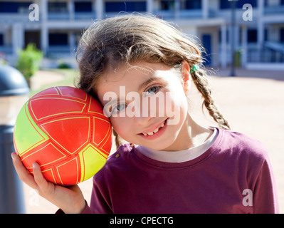 brunette little girl football player and ball smiling with blue eyes - Stock Photo