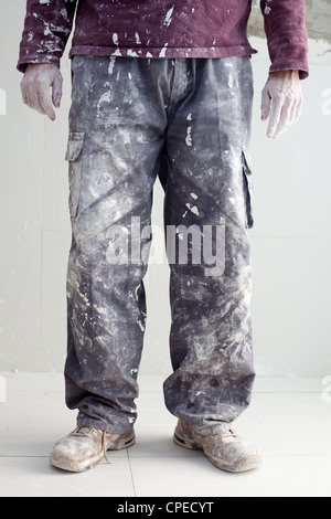 hands and white dirty trousers detail of plastering painter man - Stock Photo
