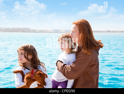 mother and daughter sister girls with dog on the sea sailing in a boat - Stock Photo