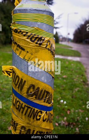 A lamppost wrapped with yellow warning tape: Caution Lighting Cable - Stock Photo