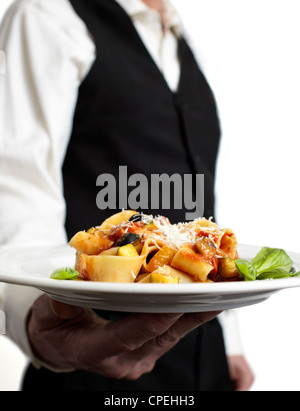 A waiter is holding a plate with pasta, tomato sauce, parmesan and basil.€ Focus on plate. Close-up. - Stock Photo