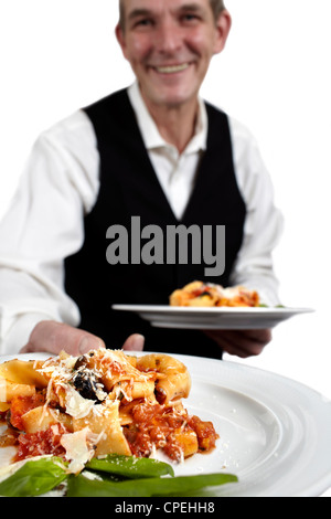 A servant is holding a plate with pasta, tomato sauce, parmesan cheese and basil.€ Focus on plate. Close-up. - Stock Photo