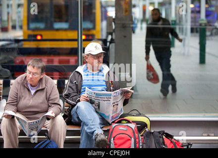 Manchester Piccadilly railway station passengers reading in waiting area - Stock Photo
