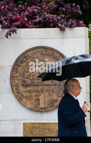 A Greek man walking  by a plaque portraying an old drachma coin that was replaced by the euro in 2002 outside Athens - Stock Photo