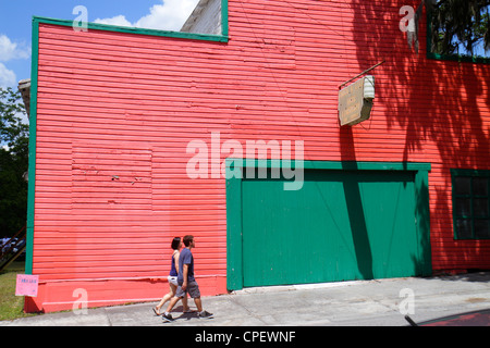 Brooksville Florida man woman couple walking red building former livery stable renovated - Stock Photo