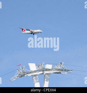 Passenger jet airplane on approach to London City Airport flying above top of Emirates cable car support pylon tower - Stock Photo
