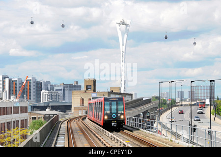 Docklands light railway train with Emirates Air Line cable car gondolas beyond - Stock Photo