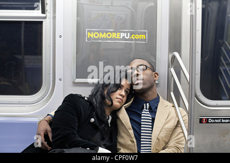 A man and woman look sleepy at night on the subway in New York City. - Stock Photo