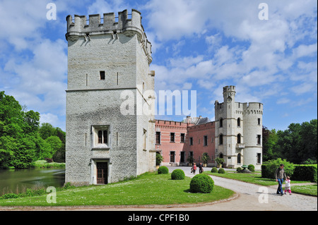 Tourists at the Bouchout Castle in Neo-Gothic style surrounded by moat in the National Botanic Garden of Belgium - Stock Photo