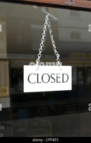 Closed sign hanging on chain in shop door window - Stock Photo