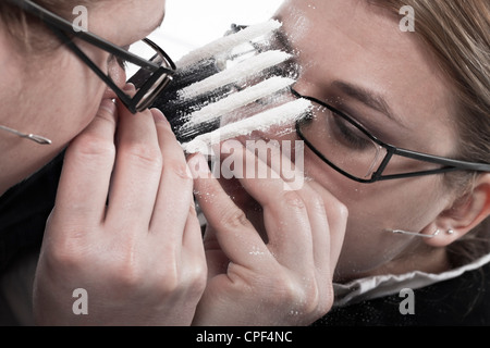 Drug addicted businesswoman reflected in mirror snorting line of cocaine. - Stock Photo