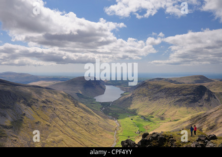 Walkers on the summit of Great Gable enjoying the view over Wasdale and Wast Water in the English Lake District - Stock Photo