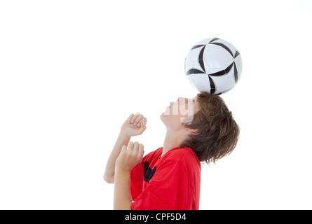young boy soccer or football player balancing ball on head - Stock Photo