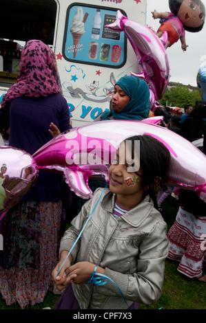 Boishakhi Mela, celebration for Bangladesh New Year. Family with pink dolphin balloons buying ice-creams - Stock Photo