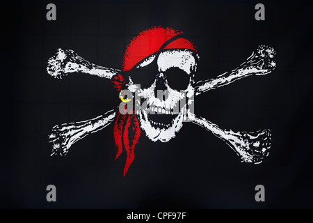 Jolly Roger pirate flag in bar window, Brixham, Devon, England - Stock Photo