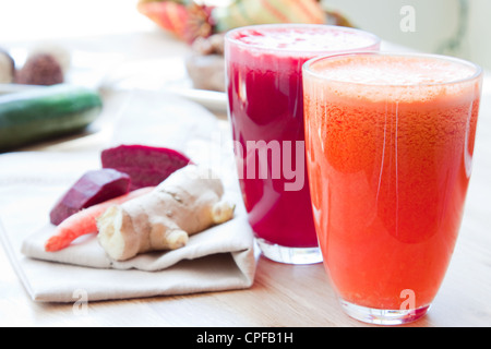 Two glasses of healthy juice - Beet, Apple, Carrot, Ginger and Orange, Apple, Pineapple. Ingredients in the background. - Stock Photo