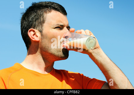 man is drinking fresh glass of milk in the blue skye - Stock Photo
