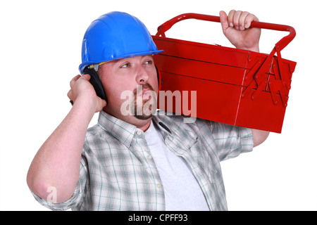 craftsman wearing headphones and carrying a tool box - Stock Photo