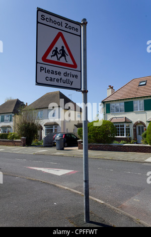 A school zone street sign in a residential district - Stock Photo