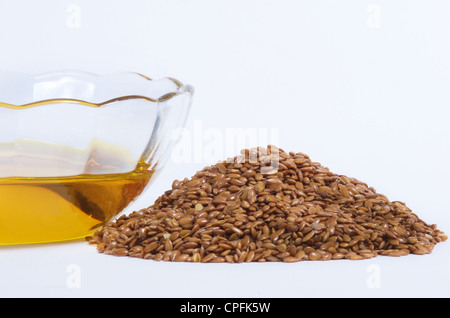 Flaxseed oil in bowl and whole flax seeds. Isolated on white. - Stock Photo